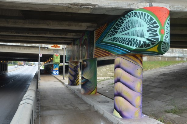 painting on bents on an underpass, a face in the middle and a hand on either side, holding onto the concrete pillars, entrance to subway TTC station in the background,