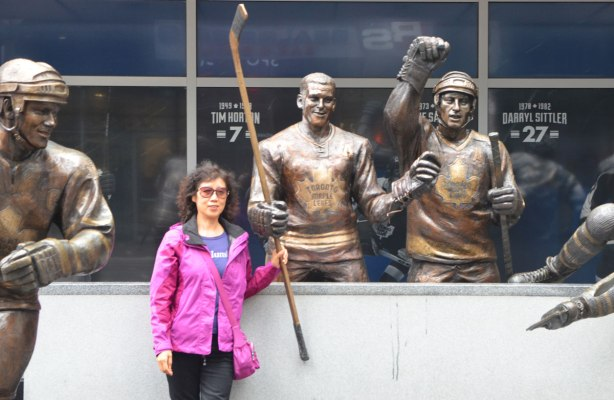 a woman in a pink jacket stands in front of a statue of a hockey player, Tim Horton.  She is holding onto his hockey stick.  There are a couple of other statues in the picture too.