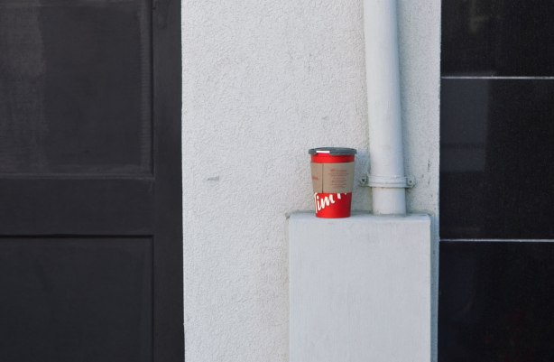 an empty red Tim Hortons coffee cup sits on a white ledge on a white wall with a black door on either side of it.