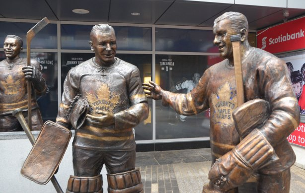 three statues of former Toronto Maple Leaf players in Legends row in Toronto, goalies Turk Broda on the right and Johnny Bower on the left, are standing, George Armstrong is in the background.