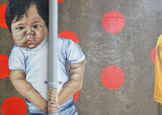 painting of a toddler on a concrete support, street art