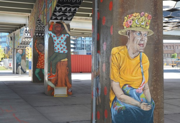 street art murals on 4 bents holding up the ramp of a highway, underpass park, the paintings are of people, in the foreground is a woman with a yellow T-shirt and a hat with little flowers