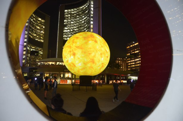 looking through the O of the Toronto sign to the yellow and orange projections on the large globe in front of City Hall, art installation from Nuit Blanch
