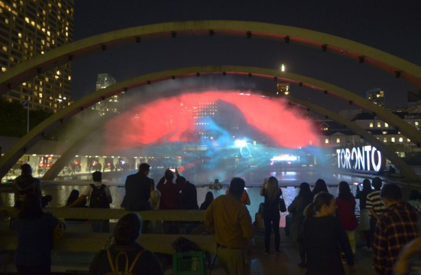 people standing around with their backs to the camera in the foreground, with a picture projected onto a wall of water under the arches at Nathan Phillips square in the background. The picture is of a blue woman on a red background.