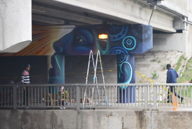 a ladder, people working on a mural of a blue face,