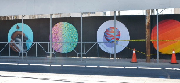 construction hoardings, painted black and on that, large circles with paintings on them.  A bird head, one with green and pink squiggles, and one with a zebra striped sphere in orange and blue and the fourth with diagonal stripes making a gradient from yellow to dark red