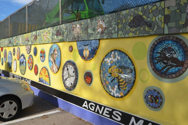A wall with a chainlink fence above it, a large green construction crane is behind the wire fence. The wall has been covered with a mural, yellow background and mosaic pictures on it. A quote runs along the bottom at ground level, white letters on black background, quote by Agnes MacPhail