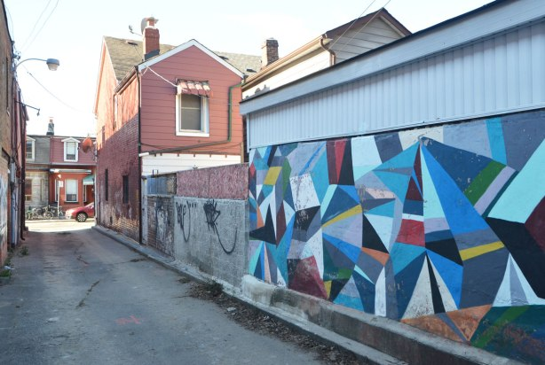 looking down an alley, an abstract mural of triangular shapes is on one wall