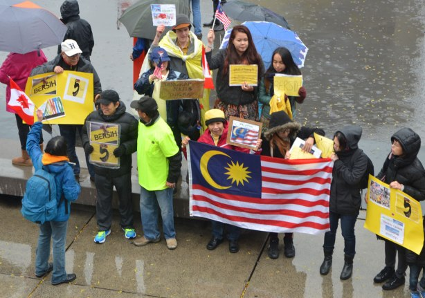 a small group of people posing for a picture with the Malaysian flag and some protest signs that say berish.