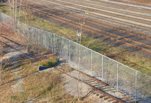 looking at the scene from a above, a blue canoe has been used to plant plants in. It lies across an old railway track, a chainlink fence separates the canoe from the main railway tracks that still function.