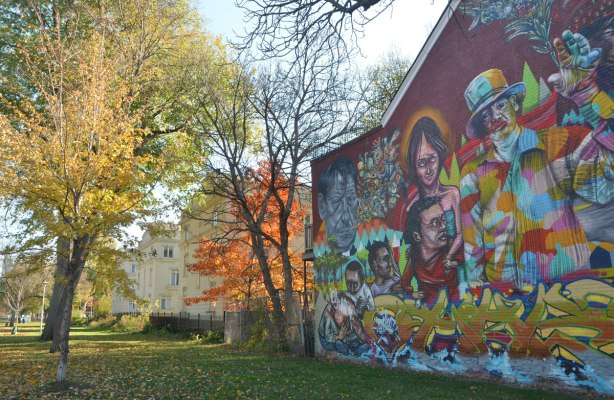 large mural on the side of a house at the edge of Alexandra Park in Toronto, painted by Elicser and Troy Lovegates, most of the mural is in the photos along with some autumn foilage trees and some newer houses in the neighbourhood