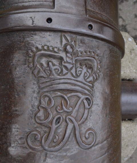 the insignia on the top of a cannon from the 1880's, markings in the brass of the cannon , royal insignia
