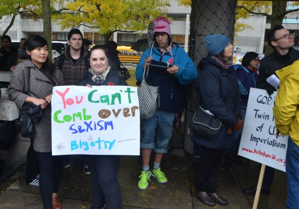 people at a protest rally a woman holds a sign that says You Can't comb over sexism and bigotry