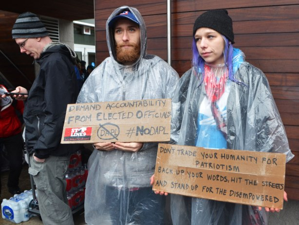 people at a rally protesting against Donald Trump as President of the USA, a young couple in clear rain ponchos each holds a brown cardboard sign
