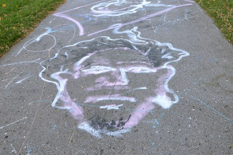 large chalk drawing of a man's face in black, white and pale purple, on a paved path in a park