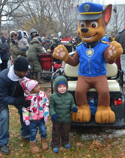 Santa Claus parade, along the beginning of the parade, off to the side, a character in a Chase costume (a character from the TV program Paw Patrol) is posing with two little kids and their father