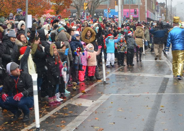people standing on the sidewalk cheering and waving at the Santa Claus parade