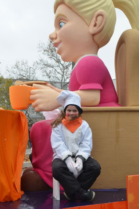 Santa Claus parade - a girl is looking cold, sitting on a float in chef's jacket and hat and large orange scarf. She is sitting beside a large sculpture of a woman sitting on a wood chair with an orange cup in her hand