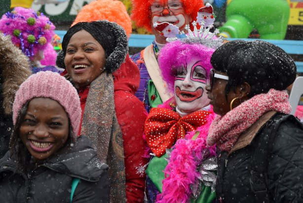 Santa Claus parade - two clowns in fuzzy hair wigs mingle amongst the crowd before the parade starts, lots of smiling faces.