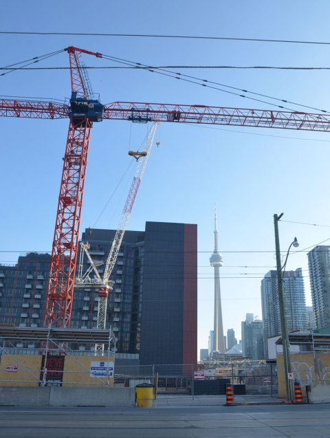 CN Tower in the distance, condo construction in the foreground, with a red crane