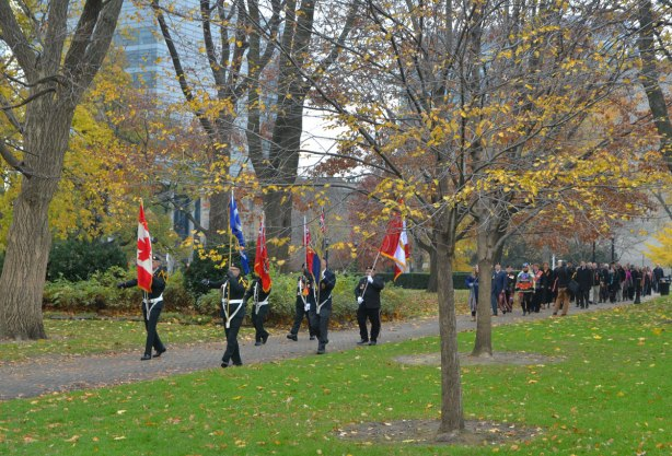 colour party of 6 men carrying flags lead a procession through the park in front of the parliament buildings at Queens Park, autumn and most of the leaves are off the trees.