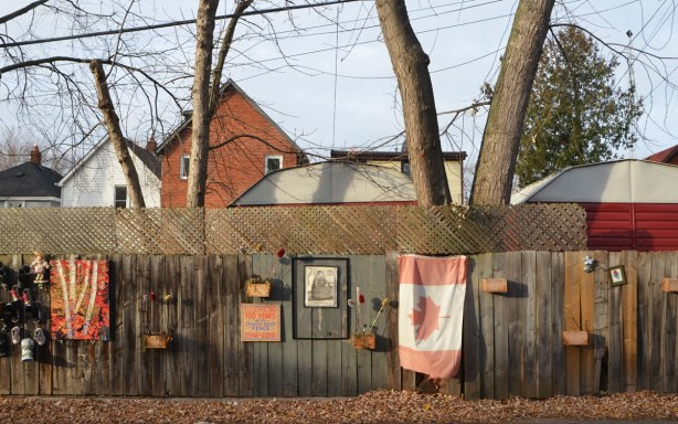 decorated wooden fence on Craven Road, a road with houses only on one side of the street, fence is decorated with a faded Canadian flag, a picture of Queen Elizabeth I, some wood planters, a painting of birch trees in autumn, old shoes, and a sign that says Craven road FEnce, 100 years, 1916 to 2016