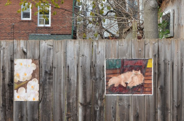 two painting on a fence. One is of a cat and the other is of white flowers