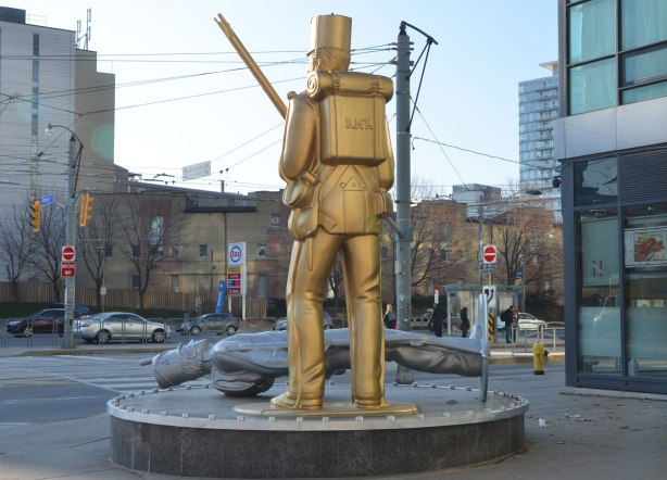 Douglas Copeland's sculpture of two tin soldiers, a gold one standing with backpack on and rifle in hand, and a silver one lying on its back on the ground, uniforms circa War of 1812, seen from the back, figures are much large than life sized and they are on a corner at an intersection, Bathurst St. and Fleet St.