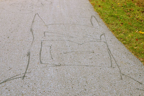 line drawing in black of Batman's head and shoulders, drawn on a paved path in a park