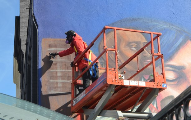 elicser painting a large mural by CP 24 parkinglot on Queen St West, showing people in the tv business - up close picture of him with a can of spray paint in his hand.