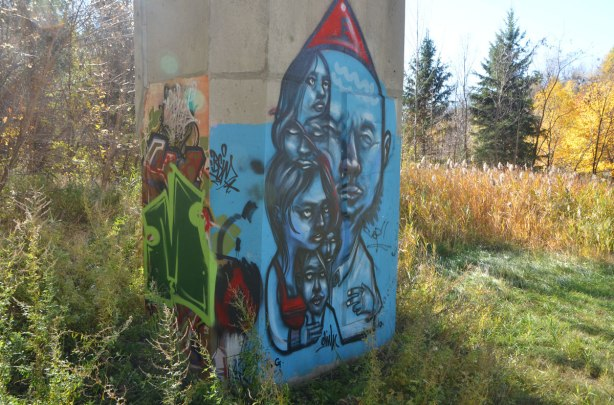street art by elicser in blue of a family. Man with red hat, woman and kids huddled together, fall park scenery in the background.