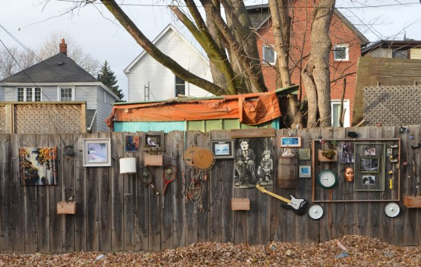 things on a fence as decoration, guitar, pictures, clock, boxes,