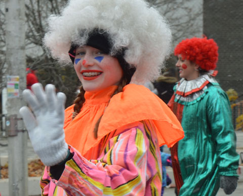 Santa Claus parade - a young woman in a clown costume with large fuzzy white wig, waves, she is wearing white gloves