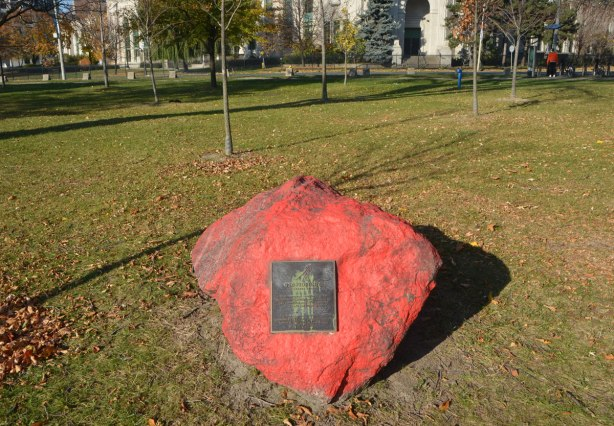 a large rock with a bronze plaque on it. The rock has been crudely painted red