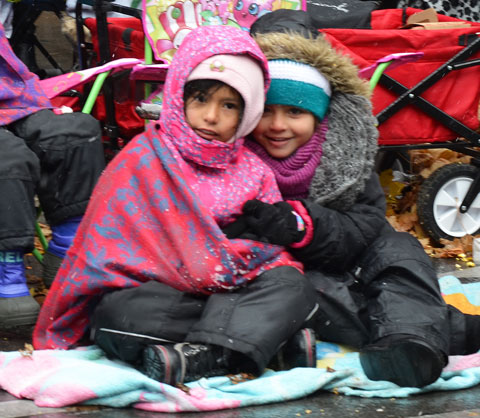 Santa Claus parade - two girls huddle under blankets and parkas while sitting on the sidewalk waiting for the parade to start