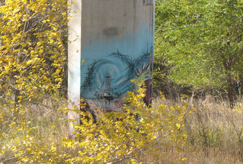 graffiti on a pillar in the park with weeds and small shrubs growing around it.