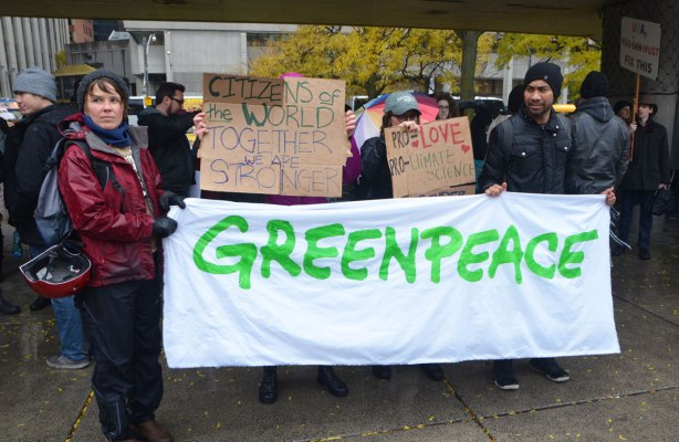 people holding a large greenpeace banner at a rally to protest against Donald Trump