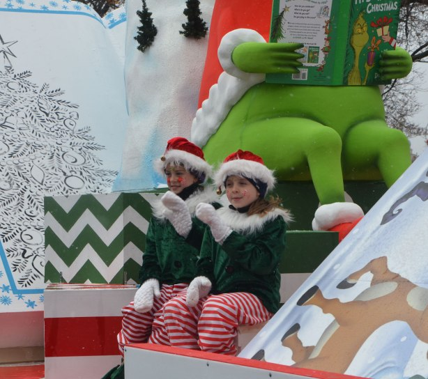two kids dresses as Christmas elves in green, red and white wave to passersby as they sit on a float with a large Grinch reading a book, Santa Claus parade