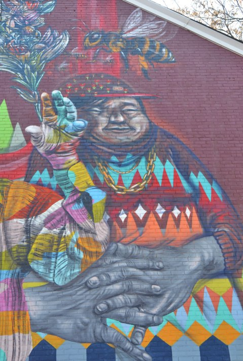 part of a larger mural of elicser and Troy Lovegates, colourful people, a heavy set man with a cap on, seated with large hands folded on his lap, wearing a sweater with rows of colourful diamond shapes. A large bee is flying above his head.