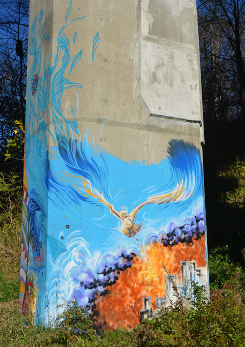 small mural on the bottom of a concrete pillar, a bird takes flight over a city at sunrise. The word hope is written on the mural