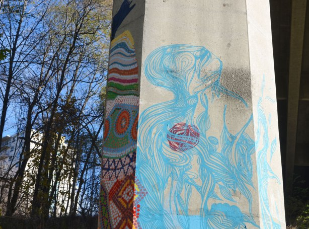 side of a concrete pillar with light blue line drawing of person looking upwards, abstracted.