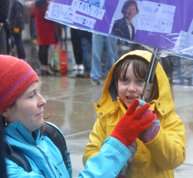 a mother helps her daughter by holding an umbrella over her while the daughter holds a protest placard that she's made herself.