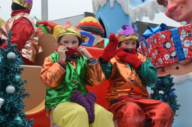Santa Claus parade - two kids in shiny orange, green, red and yellow costumes, sitting on a float in the parade, they have their hands in mitts covering their mouths and chins trying to keep warm.