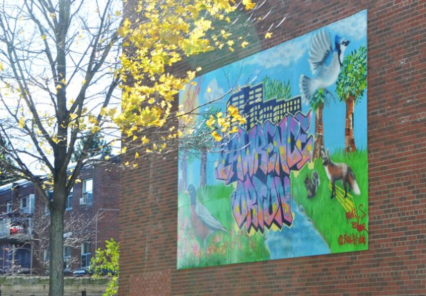 a mural on the side of a building that has the words Lawrence Orton in blue and orange. There is also a blue jay in flught, a fox and a squirrel and a robin standing in the grass.