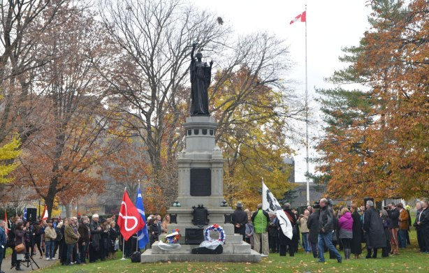 statue, memorial to those who died in the Northwest Rebellion of 1885, to the soldiers on the winning side, at Queens Park, with people around it, a flag with picture of Louis Riel is planted beside the monument,