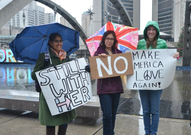 three women at a protest rally at Nathan Phillips Square in Toronto, protesting against the election of Donald Trump as American president, each holding a sign, Still with her, no, and make america love again.