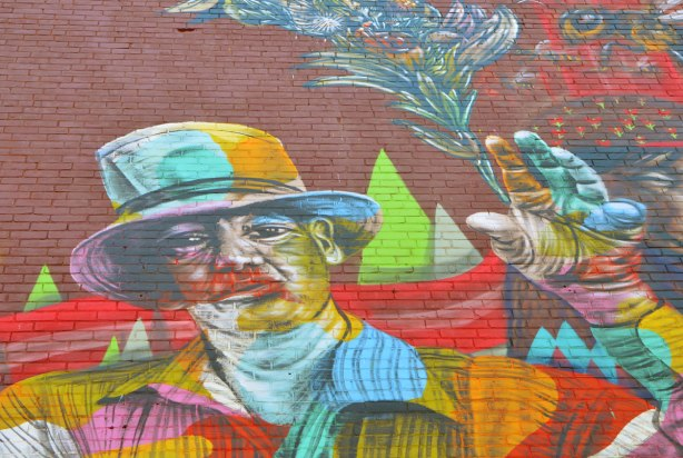 part of a larger mural of elicser and Troy Lovegates, colourful people, a man in a top hat and jacket, holding a bouquet in his upraised hand - a bouquet that looks like one a magician would use