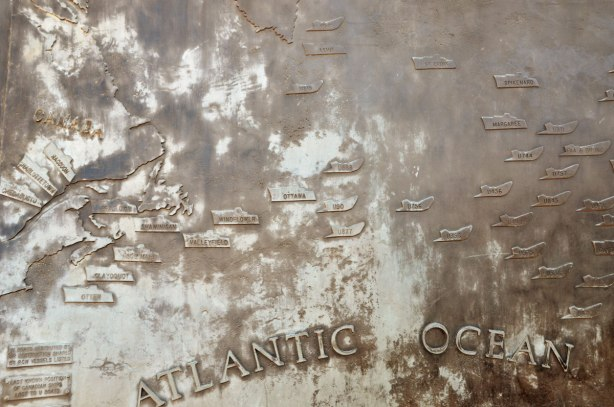 relief map of eastern Canada and the Atlantic Ocean, in bronze on a WW2 memorial. Little ships are shown on the ocean where they were sunk during WW2.