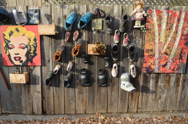 a wooden fence with many things hanging on it - an Andy Warhol Marilyn Munroe print, a painting of autumn birch trees, and many old shoes