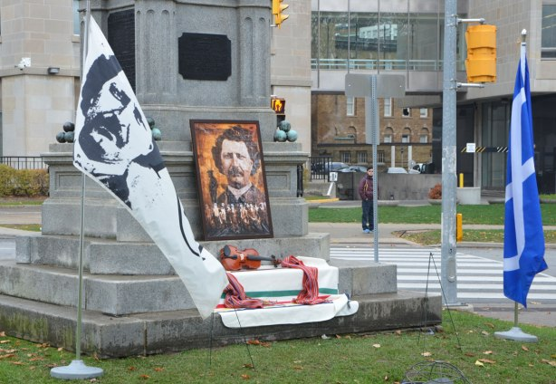 base of monument with picture of Louis Riel, a violin and a Hudsons Bay blanket on it.